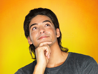 Buy stock photo View of man with hand on chin looking up against yellow background