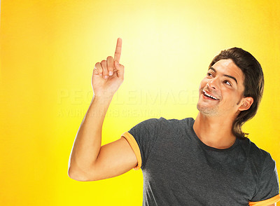Buy stock photo Handsome man smiling while pointing up