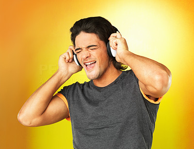 Buy stock photo Man singing while listening to headphones against yellow background