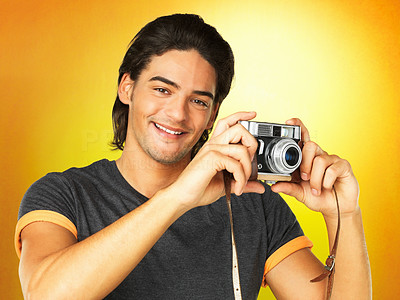 Buy stock photo A young man holding up a vintage camera against a yellow background