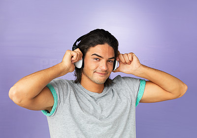 Buy stock photo Attractive man smiling while listening to headphones
