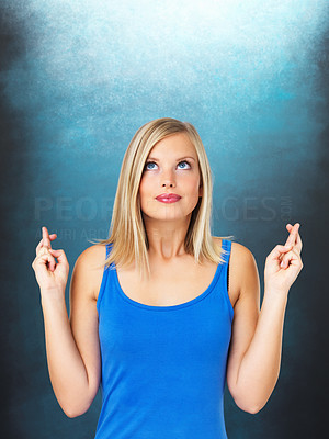 Buy stock photo Young woman with crossed fingers on blue background