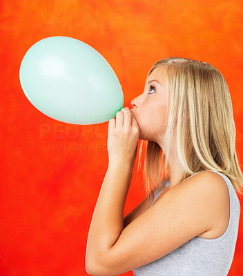 Buy stock photo Side view of young woman blowing balloon on orange background