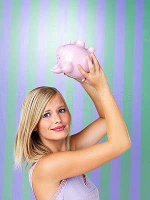 Buy stock photo Pretty woman checking her piggybank for money