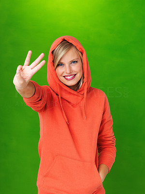 Buy stock photo Portrait of pretty woman in hooded sweatshirt holding up three fingers