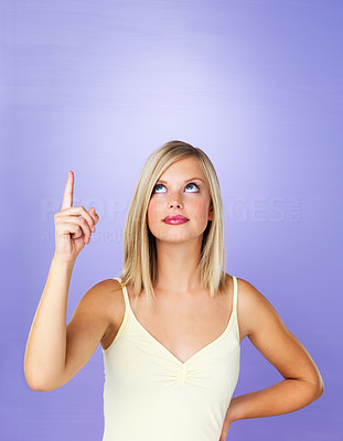 Buy stock photo Portrait of attractive woman pointing up at copyspace