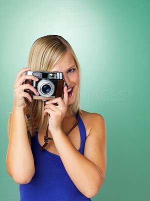 Buy stock photo A pretty young woman taking a photo with a vintage camera
