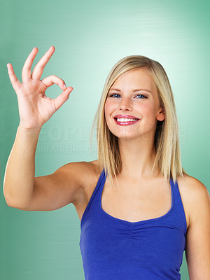 Buy stock photo Woman standing against green background giving ok sign