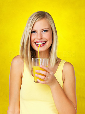 Buy stock photo Attractive woman sipping orange juice against yellow background