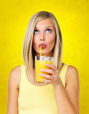 Buy stock photo Pretty woman sipping orange juice against a bright yellow background
