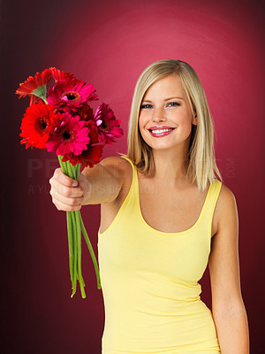 Buy stock photo Attractive blonde holding out bouquet of flowers
