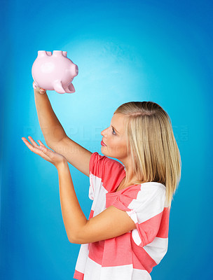 Buy stock photo Side view of blonde woman holding piggybank upside down