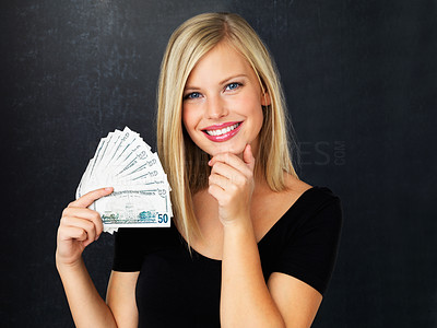 Buy stock photo Pretty woman smiling while holding fan made of money