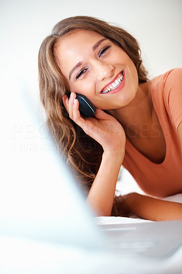 Buy stock photo Happy girl on the phone with laptop in front of her