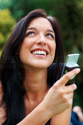 Buy stock photo Portrait of a happy young female looking away while text messaging on cellphone - Outdoor
