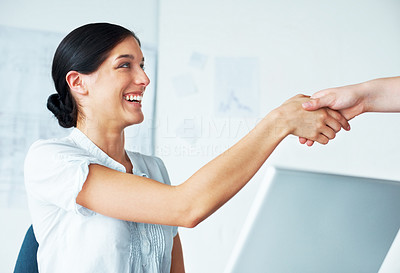 Buy stock photo Portrait of a pretty young female business executive shaking hands with associate in the office