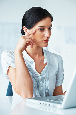 Buy stock photo Portrait of a beautiful young woman thinking while working on laptop in the office