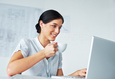 Buy stock photo Portrait of a happy young business woman drinking coffee while working on laptop in office