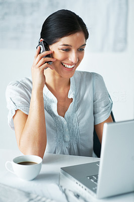 Buy stock photo Portrait of a smart young businesswoman using laptop while speaking on cellphone in office