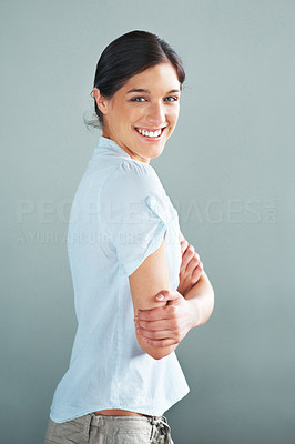 Buy stock photo Portrait of a happy young girl standing with folded hand against grey background