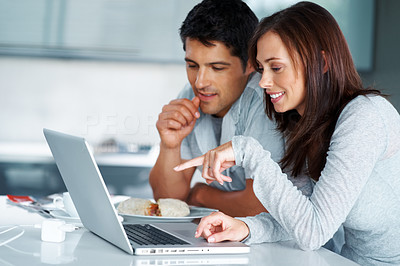 Buy stock photo A smiling young couple using a laptop together in their kitchen