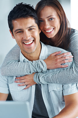 Buy stock photo Portrait of a beautiful young female hugging her boyfriend from behind while using laptop