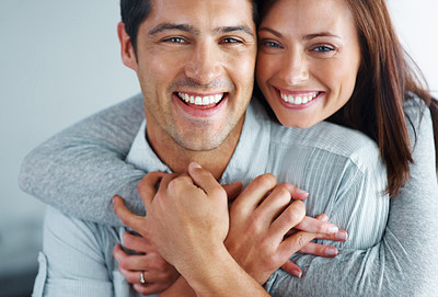 Buy stock photo Closeup portrait of a cute young girl hugging her boyfriend from behind and smiling