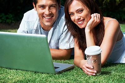 Buy stock photo Portrait of a happy young couple lying on some grass with their laptop in the park - Outdoor