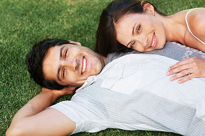 Buy stock photo Portrait of a happy young couple lying on grass and looking at you - Outdoor