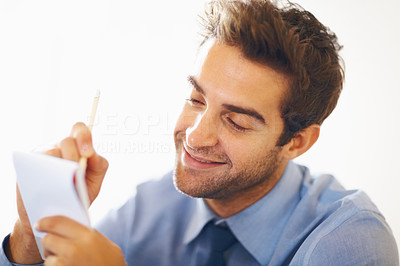 Buy stock photo Closeup portrait of smiling young executive noting down in notepad