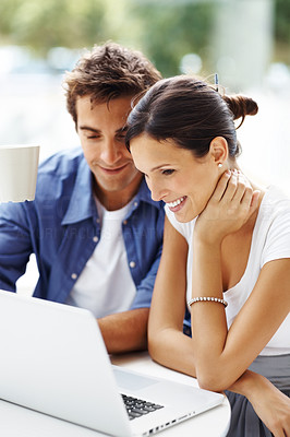 Buy stock photo Happy young couple working on a laptop and having a cup of coffee