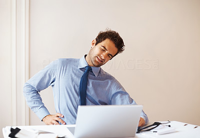 Buy stock photo Young business man sitting in front of laptop with severe back pain - copyspace