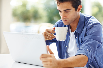 Buy stock photo Portrait of young man drinking coffee and using a laptop at home - Copyspace