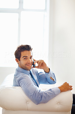 Buy stock photo Portrait of smiling executive sitting while on phone