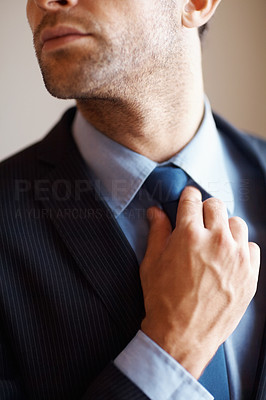 Buy stock photo Closeup of executive adjusting his tie indoors