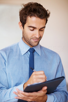 Buy stock photo Businessman smiling while making notes on clipboard
