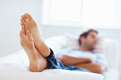 Buy stock photo Man lying down on sofa, focus on feet