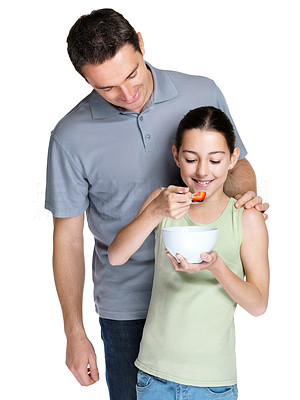 Buy stock photo Portrait of a cute little girl eating fruit salad while standing with her father against white background