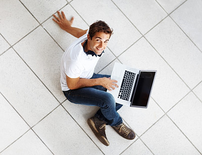Buy stock photo Top view of smiling young male sitting on floor with a computer laptop