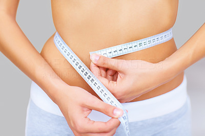 Buy stock photo Cropped image of caucasian woman measuring her waistline with a measuring tape