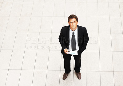 Buy stock photo High angle view of business man standing alone with report