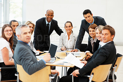 Buy stock photo Group of executives meeting around a table with laptops