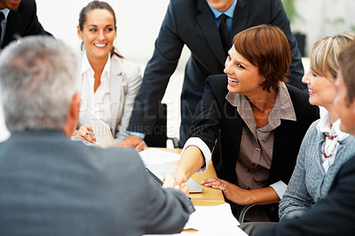 Buy stock photo Young female executive shaking hands with partner during a meeting