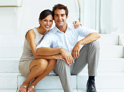Buy stock photo Portrait of happy young man and woman sitting on stairs of a building