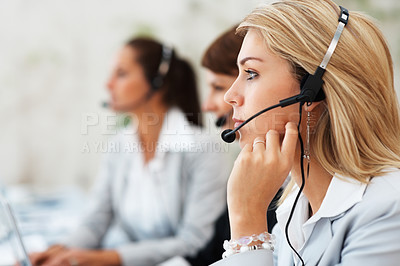 Buy stock photo Focus on customer service executive with colleagues in background