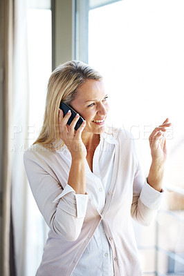 Buy stock photo Portrait of a pretty young woman talking on mobile phone and looking away through window -Indoor