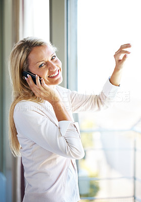 Buy stock photo Portrait of a beautiful young lady talking on cellphone looking happy standing by a window