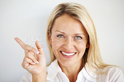 Buy stock photo Closeup portrait of beautiful young woman pointing her finger towards copyspace
