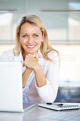Buy stock photo Portrait of a pretty businesswoman sitting at her desk with a laptop looking happy