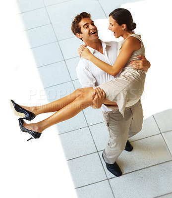 Buy stock photo Top view of happy young man carrying his girlfriend in his arms